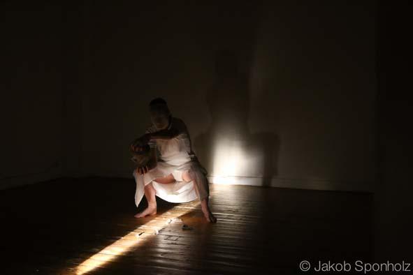 Ein Lcihtstrahl fällt in einen Raum, über eine weiß gekleidete, hockende Figur